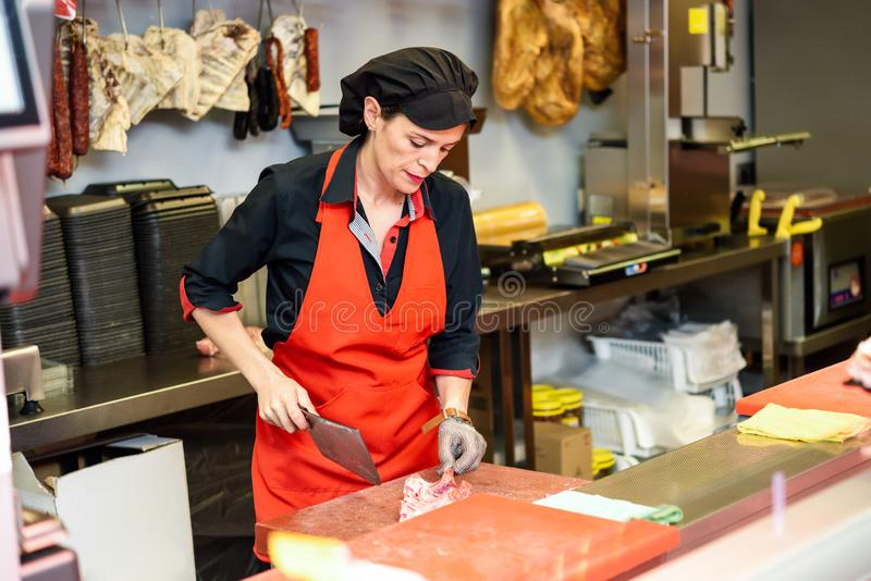 Vrouwelijk slagers scherp vlees bij teller in slachterij stock foto