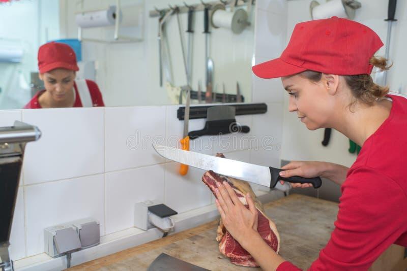 Vrouwelijk slagers snijdend vlees stock afbeelding