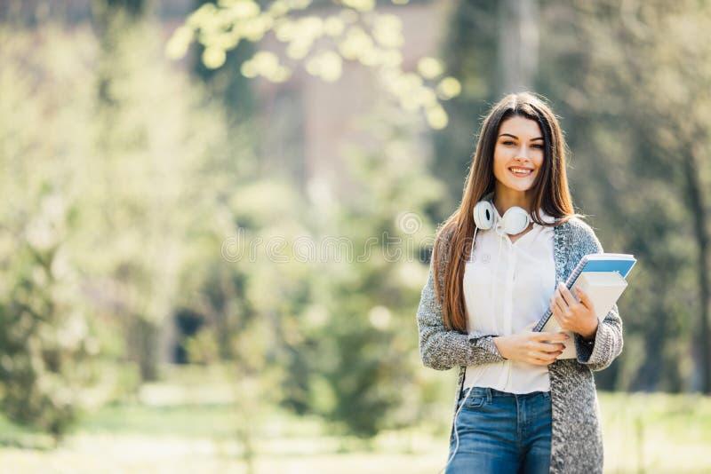 Vrouwelijk studentenmeisje buiten met hoofdtelefoons die met notitieboekjes in park lopen royalty-vrije stock fotografie