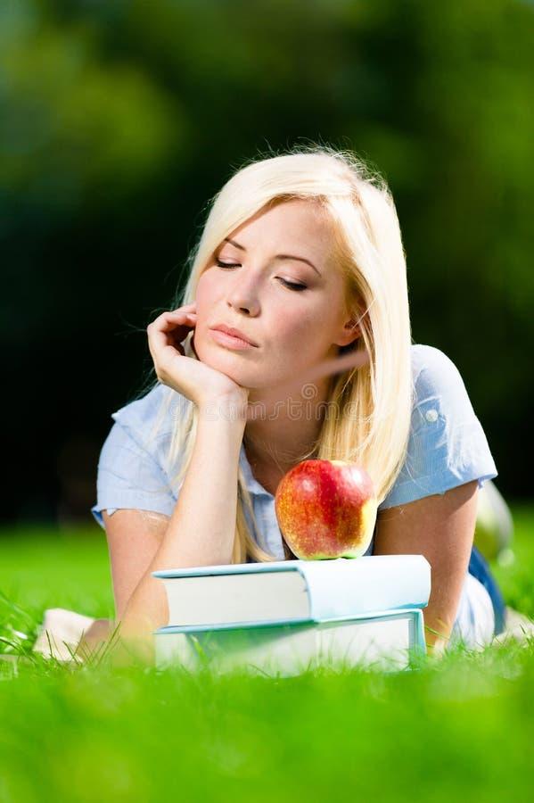 Vrouwelijk studentenmeisje op gras dichtbij de stapel van boeken stock afbeeldingen