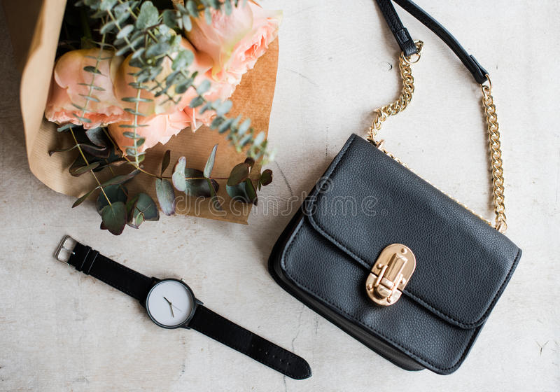 Vrouwelijk tafelblad, bloemen, elegante handtas stock foto