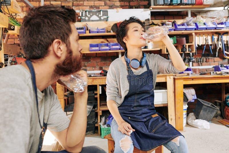 Vrouwelijk timmermans drinkwater stock foto