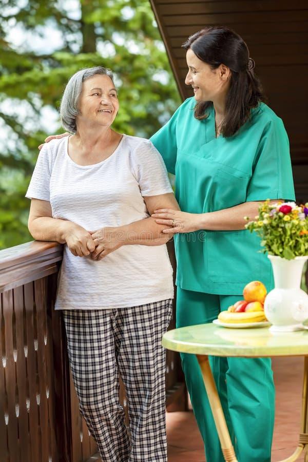 Vrouwelijk verpleegsters troostend bejaarde thuis stock fotografie