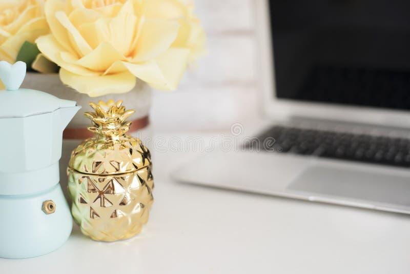 Vrouwelijk werkplaatsconcept Freelance werkruimte met laptop, bloemen, gouden ananas Blogger het werken Helder, geel en gouden stock fotografie