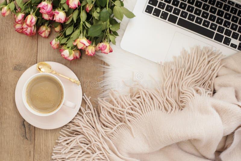 Vrouwelijk werkplaatsconcept Freelance werkruimte met laptop, bloemenrozen Blogger het werken stock foto