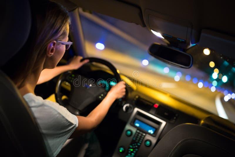 Vrouwelijke aandrijving die een auto drijven bij nacht royalty-vrije stock fotografie