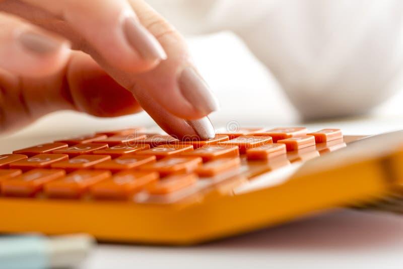 Vrouwelijke accountant of bankier die berekeningen op oranje bureau c maken stock afbeeldingen