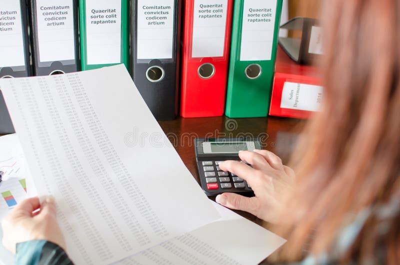 Vrouwelijke accountant die financiële documenten controleren stock afbeeldingen