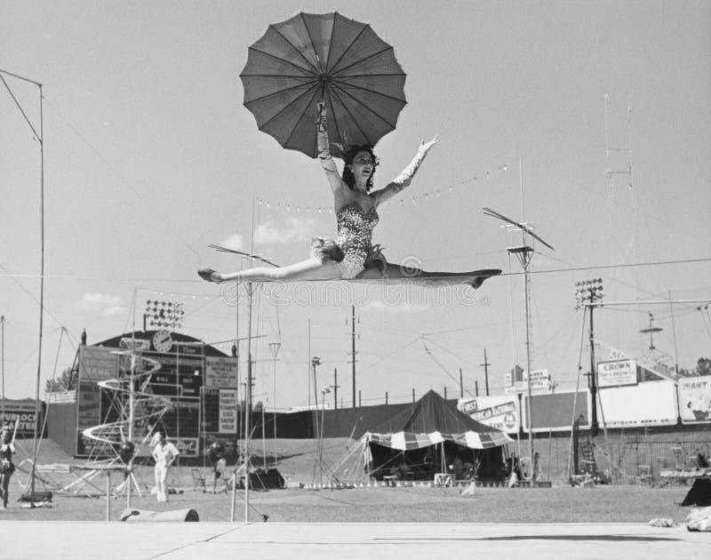 Vrouwelijke acrobaat die spleten op strak koord doen (Alle afgeschilderde personen leven niet langer en geen landgoed bestaat Th  stock fotografie