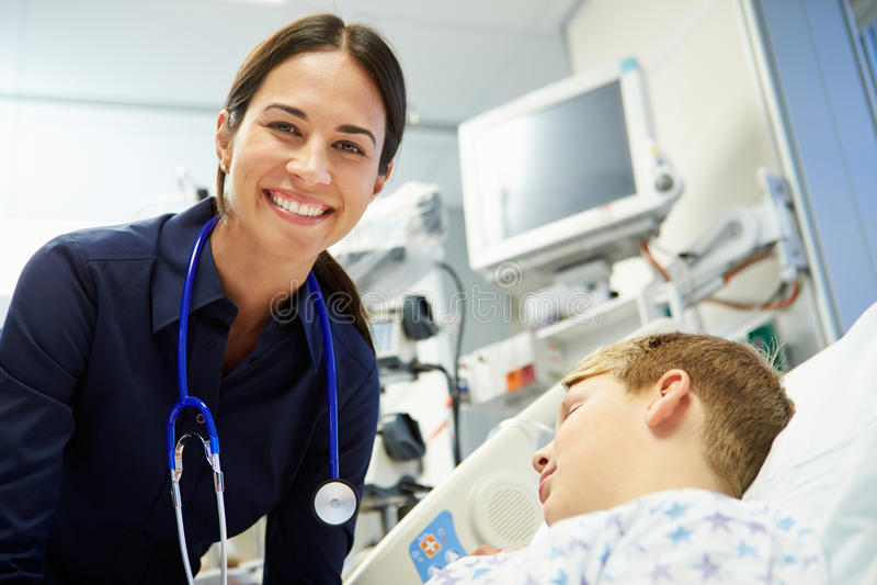 Vrouwelijke Adviseur With Sleeping Patient in Noodsituatiezaal stock fotografie