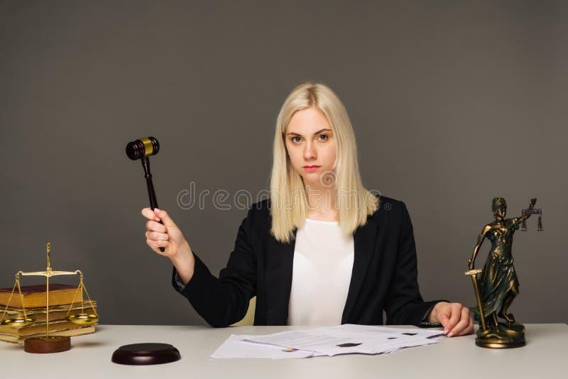 Vrouwelijke advocaat die bij lijst in bureau werken stock foto