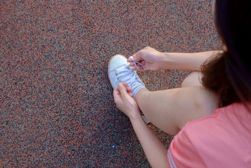 Vrouwelijke agent die haar sportschoen binden stock fotografie