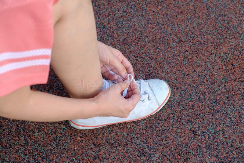Vrouwelijke agent die haar sportschoen binden stock afbeelding