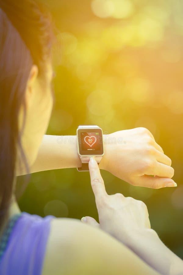 Vrouwelijke agent die harttarief in openlucht controleren op slim horloge stock foto