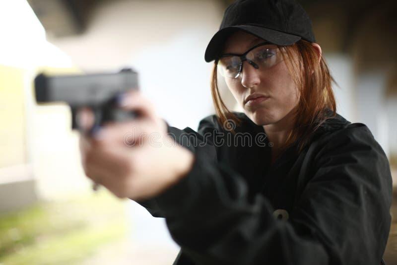 Vrouwelijke Ambtenaar die pistool streeft royalty-vrije stock afbeeldingen