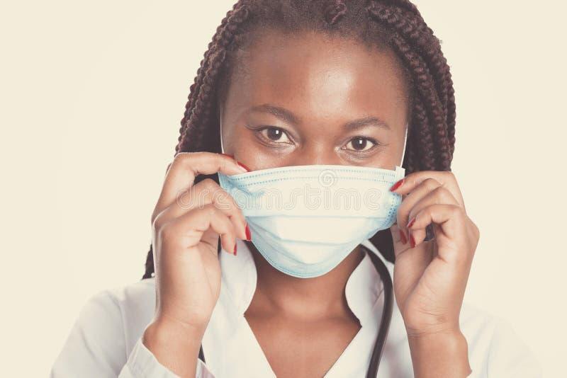 Vrouwelijke Amerikaanse Afrikaanse arts, verpleegstersvrouw die medische laag met stethoscoop en masker dragen Gelukkig opgewekt  royalty-vrije stock foto