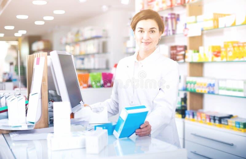 Vrouwelijke apotheker die hulp bieden bij teller in apotheek royalty-vrije stock foto