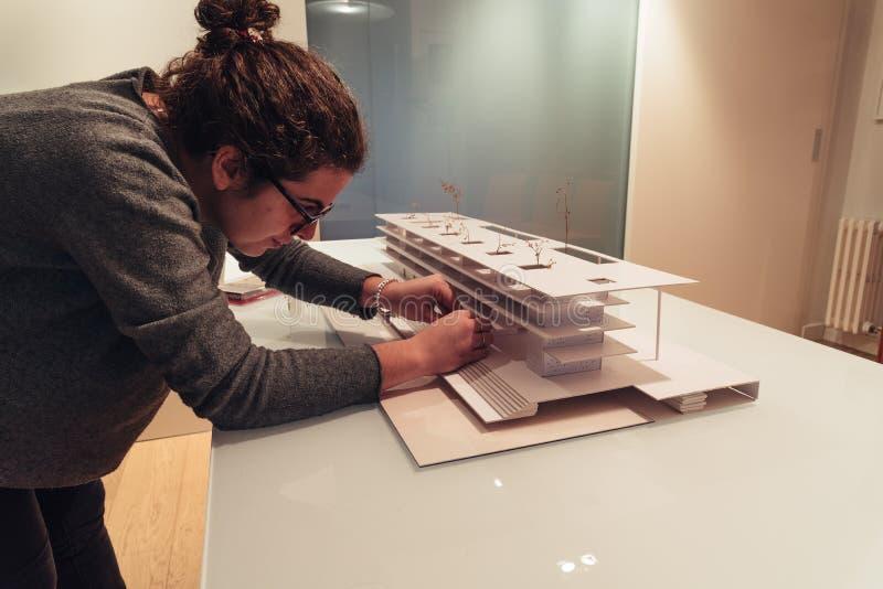 Vrouwelijke architect die aan architectuurmodel werken op lijst stock afbeelding