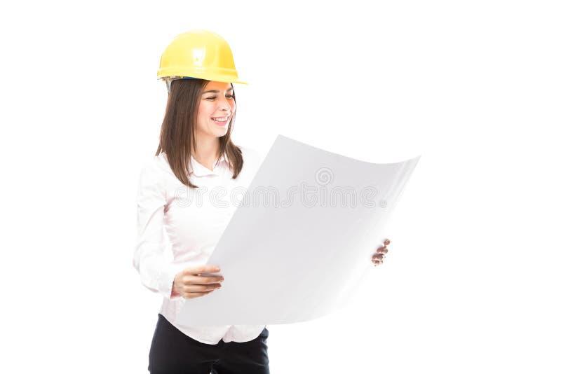 Vrouwelijke architect die blauwdrukken bekijkt stock afbeeldingen