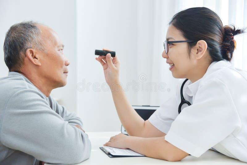Vrouwelijke Arts die aan hogere mensen geduldige ogen controleren stock foto's