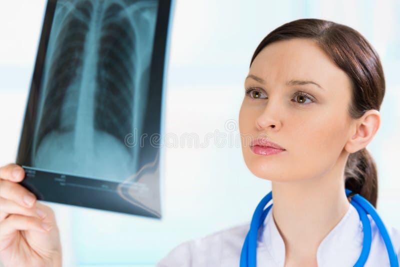 Vrouwelijke arts die bekijken longen of torsoröntgenstraal stock fotografie