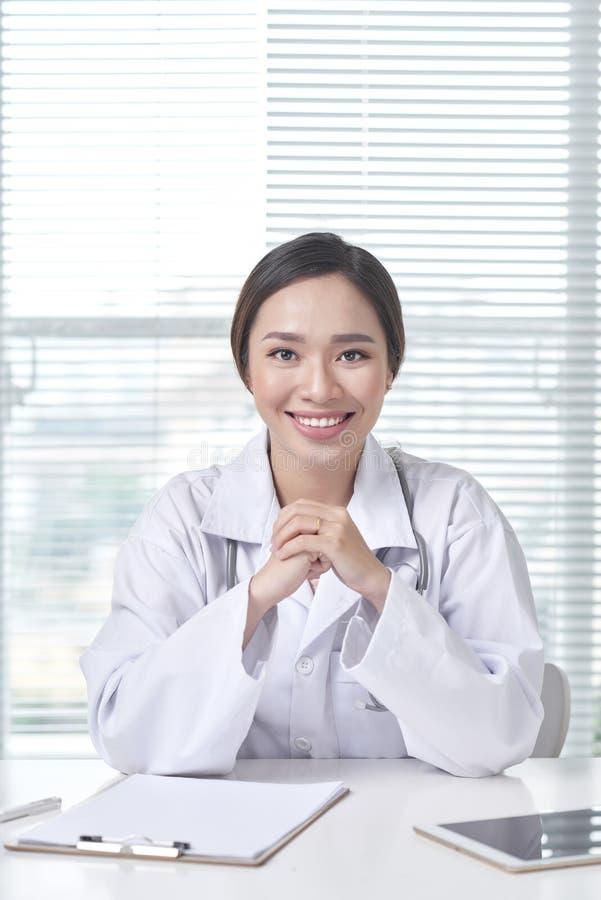 Vrouwelijke arts die bij bureau werken en bij camera glimlachen royalty-vrije stock afbeeldingen