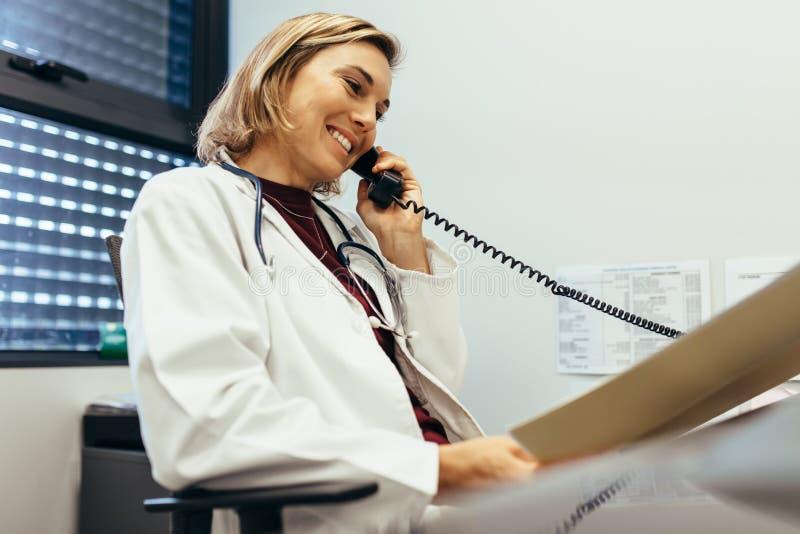 Vrouwelijke arts die bij haar bureau werken royalty-vrije stock foto's
