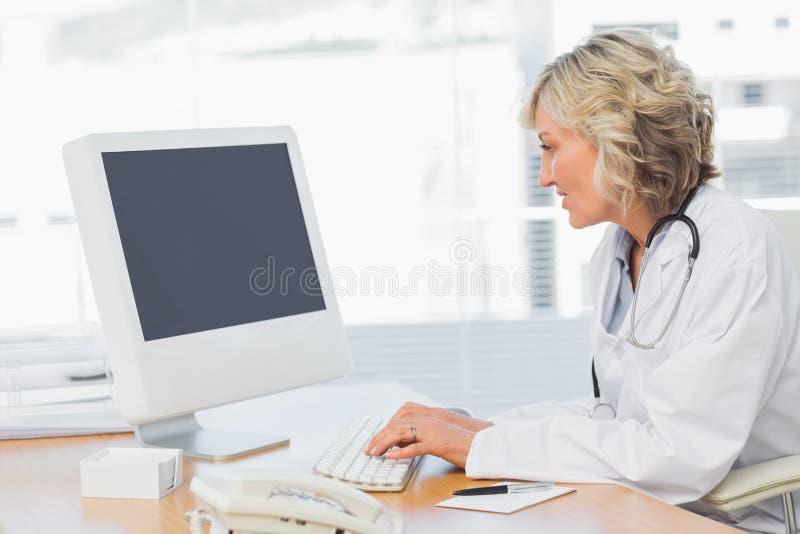 Vrouwelijke arts die computer in medisch bureau met behulp van royalty-vrije stock foto's