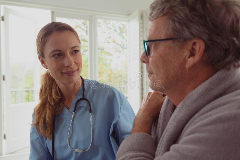 Vrouwelijke arts die de actieve hogere mens in een comfortabel huis troosten stock foto