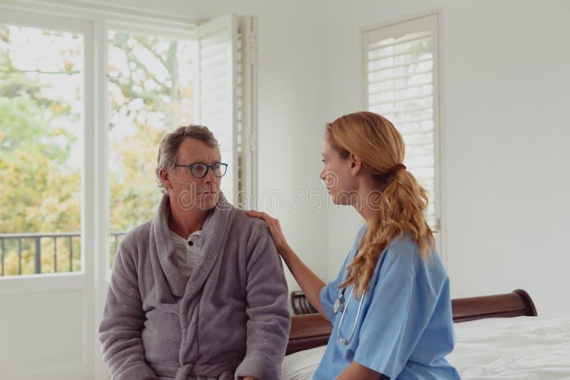 Vrouwelijke arts die de actieve hogere mens in een comfortabel huis troosten stock afbeeldingen