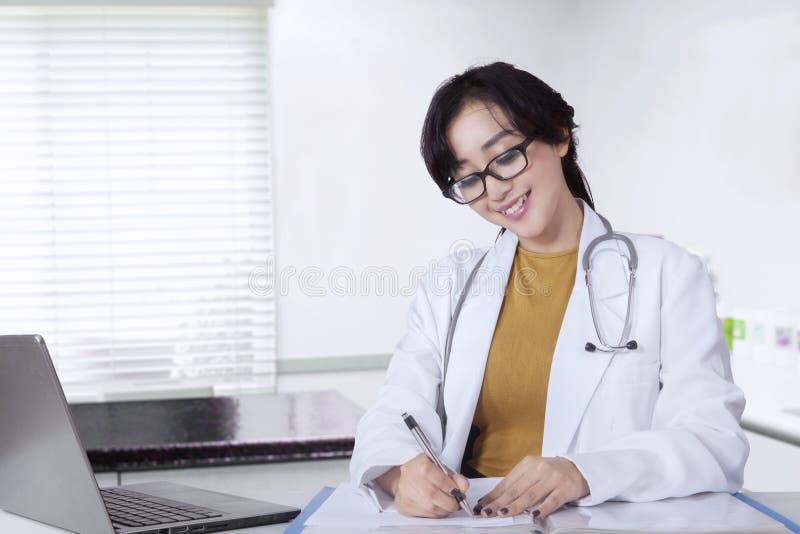 Vrouwelijke arts die in de kliniekruimte werken stock afbeelding