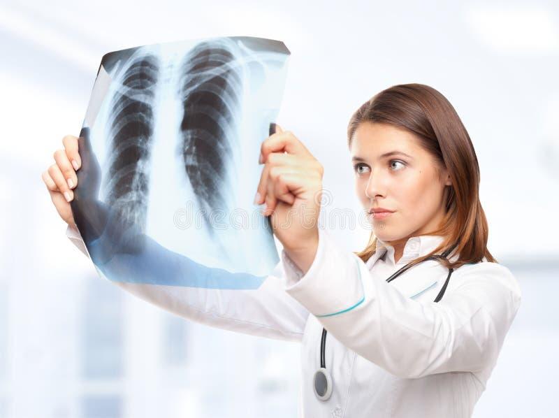 Vrouwelijke arts die de röntgenstraal bekijken stock foto