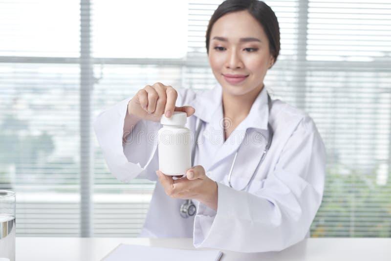 Vrouwelijke arts die een doos van pillen in medisch bureau houden stock fotografie