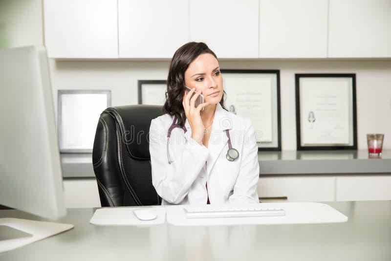 Vrouwelijke arts die een ernstig telefoongesprek nemen stock fotografie