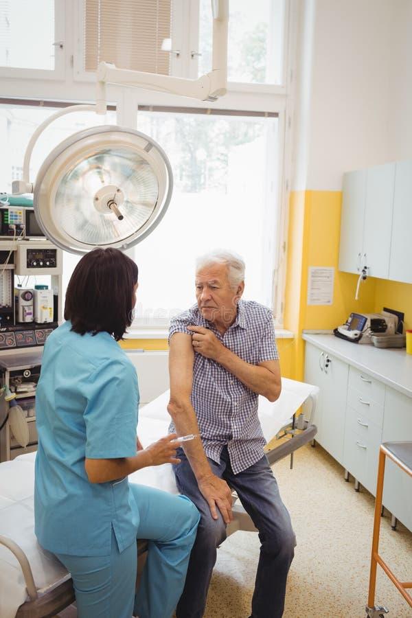 Vrouwelijke arts die een injectie geven aan een patiënt royalty-vrije stock foto's