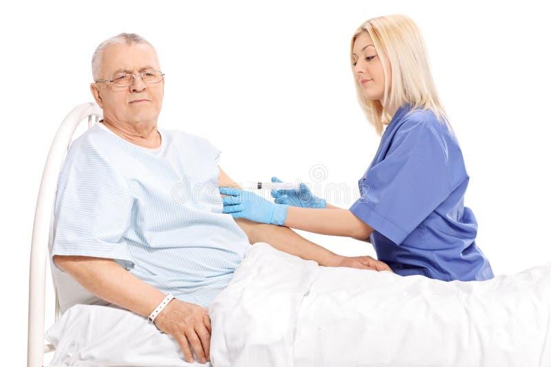Vrouwelijke arts die een injectie geven aan een rijpe patiënt stock afbeeldingen