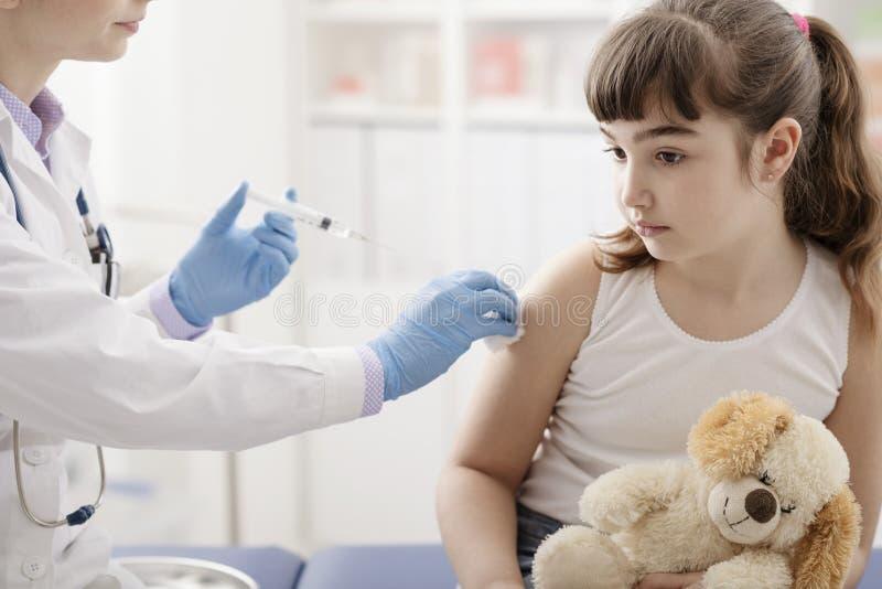Vrouwelijke arts die een injectie geven aan een jong leuk meisje stock afbeeldingen
