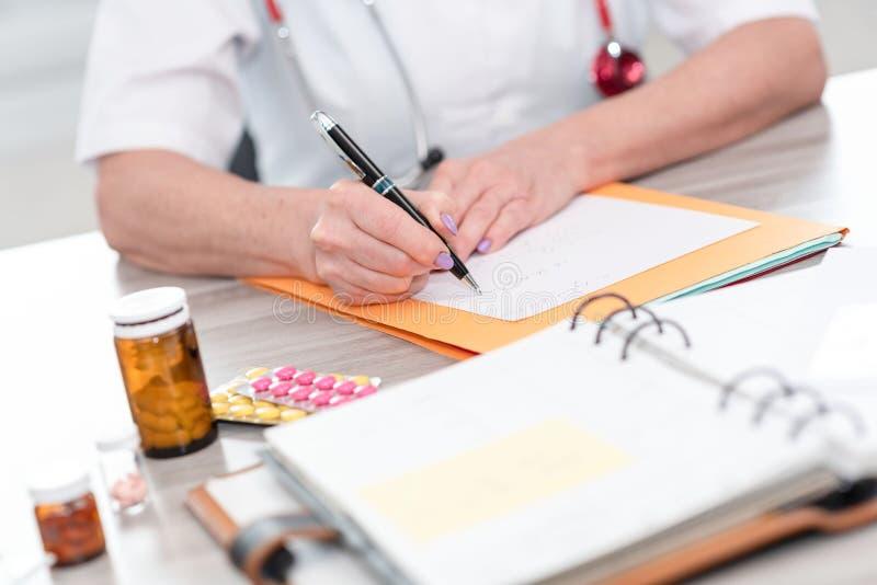 Vrouwelijke arts die een medisch voorschrift schrijven royalty-vrije stock foto's