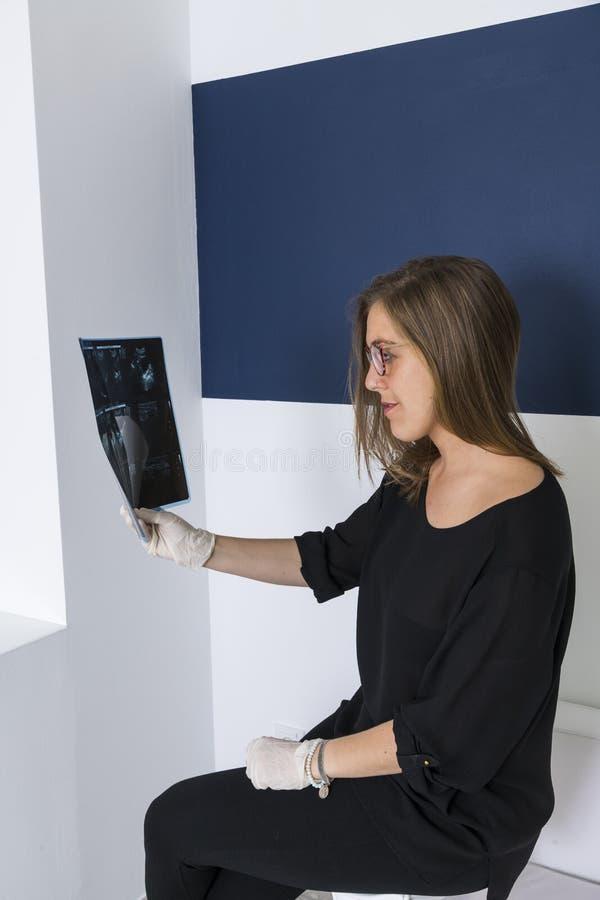 Vrouwelijke arts die een röntgenstraal bekijkt royalty-vrije stock foto