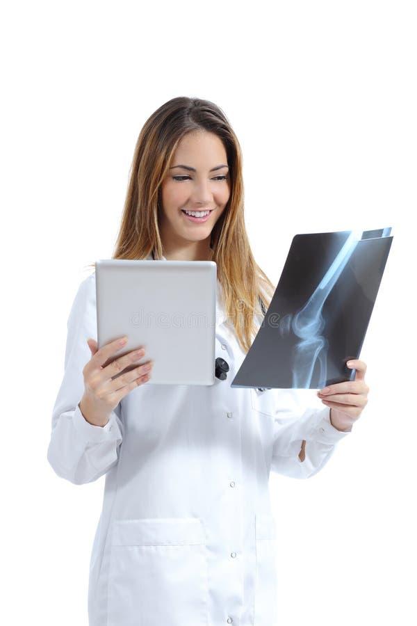 Vrouwelijke arts die een tabletbeeld vergelijken met een radiografie stock fotografie