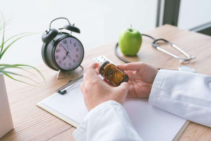 Vrouwelijke arts die fles zonder etiket van diverse pillen en medi houden royalty-vrije stock afbeeldingen