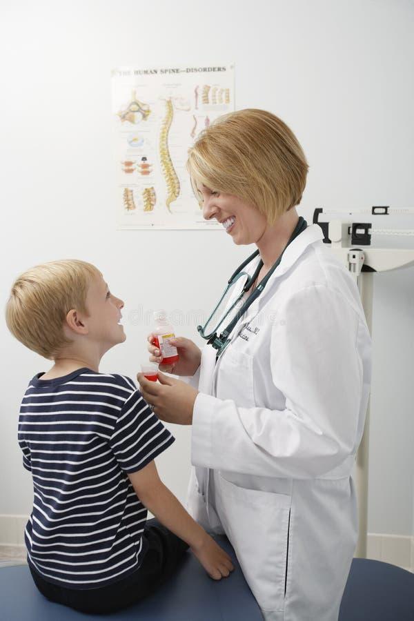 Vrouwelijke arts die geneeskunde geven aan een jongen royalty-vrije stock foto's