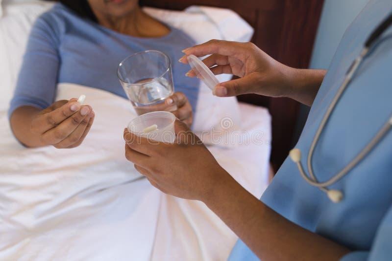 Vrouwelijke arts die geneeskunde thuis geven aan hogere vrouw in slaapkamer royalty-vrije stock afbeeldingen
