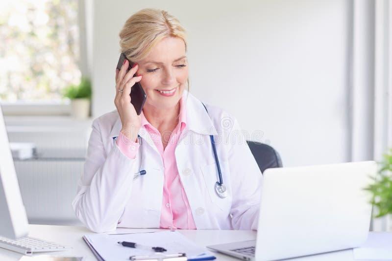 Vrouwelijke arts die haar patiënt op mobiele telefoon raadplegen stock foto's