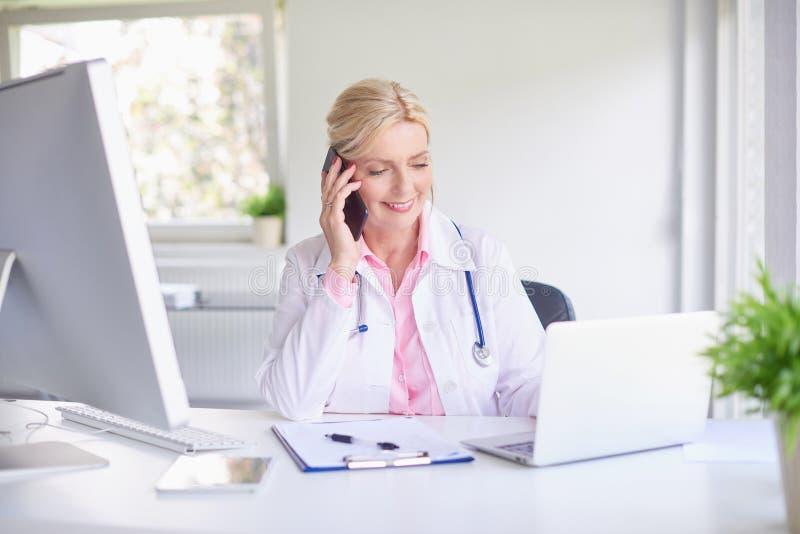 Vrouwelijke arts die haar patiënt op mobiele telefoon raadplegen royalty-vrije stock foto