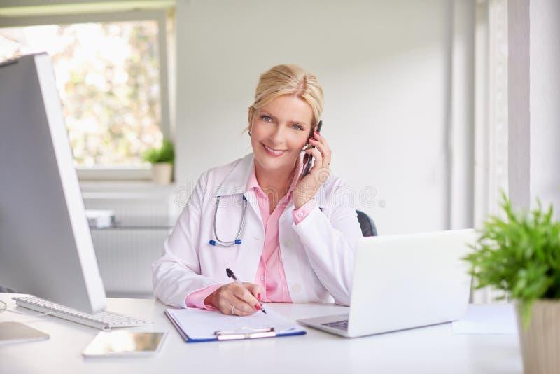 Vrouwelijke arts die haar patiënt op mobiele telefoon raadplegen royalty-vrije stock foto's