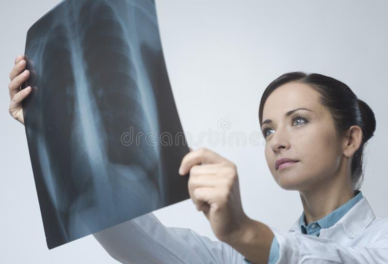 Vrouwelijke arts die het beeld van de Röntgenstraal onderzoekt royalty-vrije stock foto