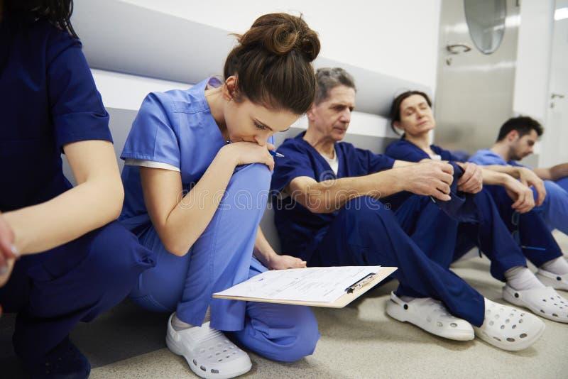 Vrouwelijke arts die het medische dossier onderzoeken royalty-vrije stock afbeeldingen