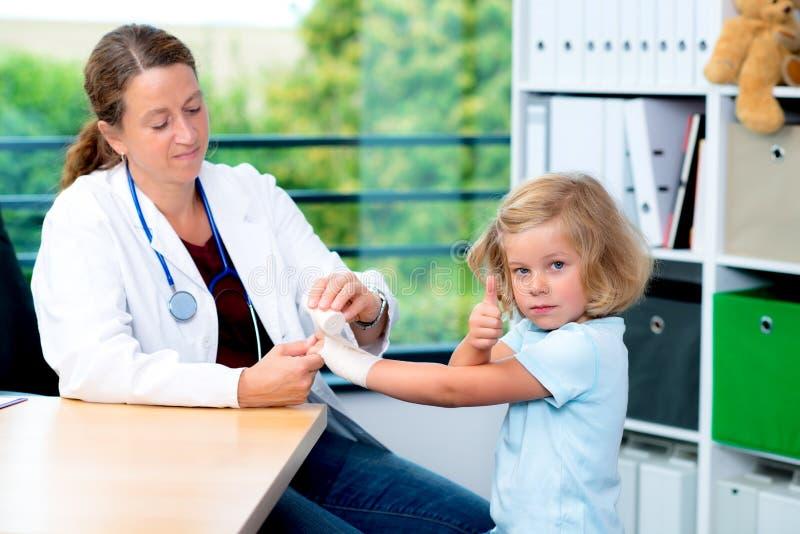 Vrouwelijke arts die het wapen van een klein meisje verbinden stock afbeeldingen