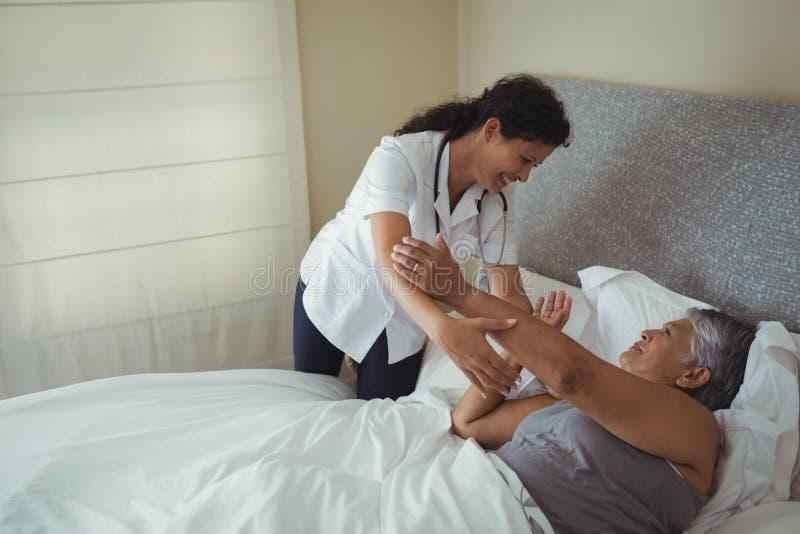 Vrouwelijke arts die hogere vrouw op bed troosten stock foto